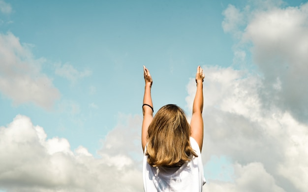 Girl against the blue sky, stands with her back and pulls her hands up.