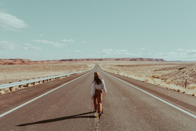 Девушка одна гуляет по дороге