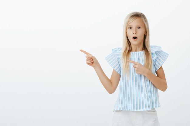 Girl amazed seeing magician trick. portrait of fascinated admiring young blond daughter in trendy blue blouse, saying wow, pointing left with index finger, feeling astonished, gasping over gray wall