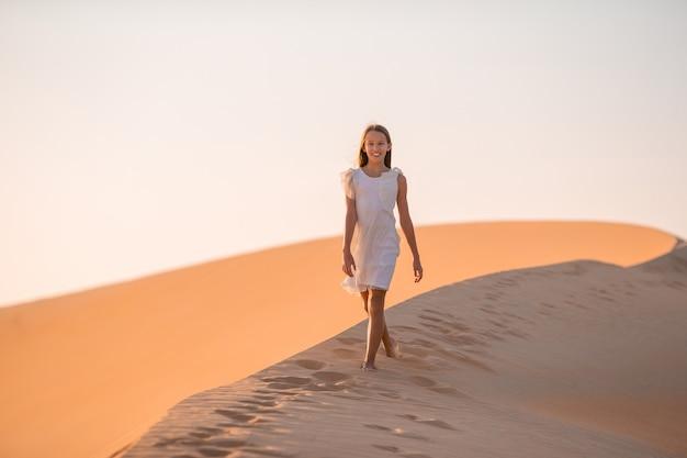 아랍 에미리트에서 사막에서 모래 언덕 가운데 소녀