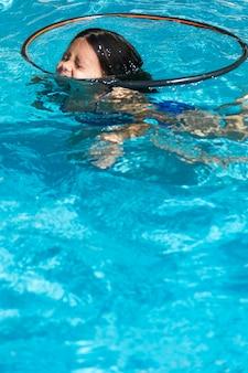 Girl among hula hoop swimming in pool