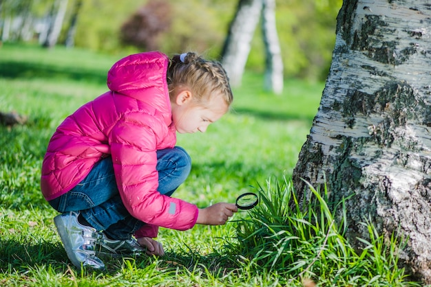 Girl analyzing the lawn with a magnifying glass