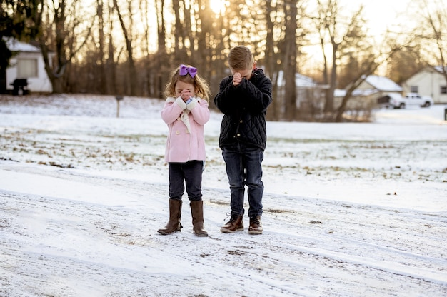 日没時に立って祈る少女と少年