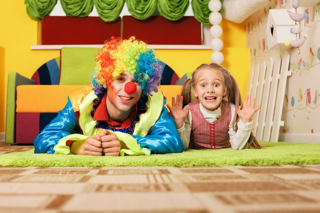 Девушка и клоун лежат на зеленом ковре.