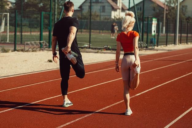 Девушка и парень делают разминку перед спортивными упражнениями на школьном стадионе
