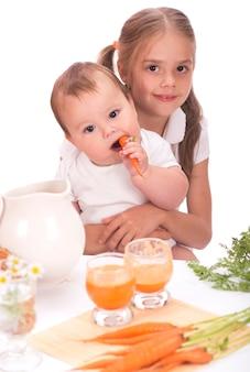소녀와 어린 소년 형제와 자매와 당근 주스 흰색 배경에 고립 프리미엄 사진