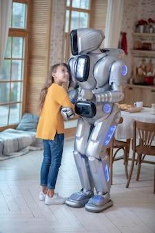 Девушка и большой робот на кухне обнимают друг друга