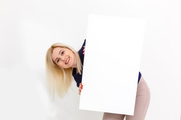Девушка и чистый холст. скопируйте место на холсте для изображения или сообщения. молодая женщина, глядя на плакат макета и стоя на сером фоне.