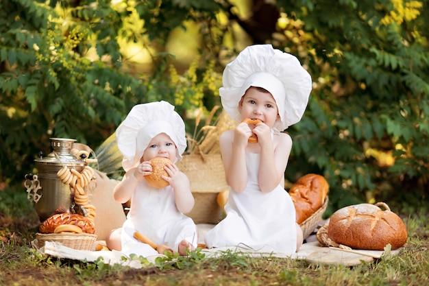 女の子と男の子は自然の中で調理します。幼児のパン屋は白いエプロンでパンとベーグルを食べる