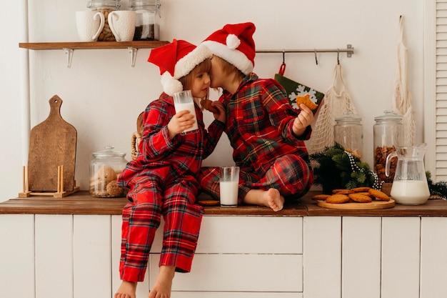 Девочка и мальчик едят рождественское печенье и пьют молоко