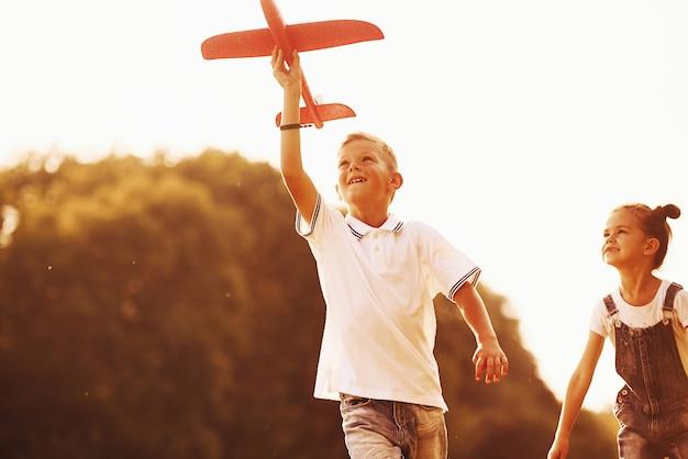 빨간 장난감 비행기를 손에 들고 야외에서 즐거운 시간을 보내는 소녀와 소년.