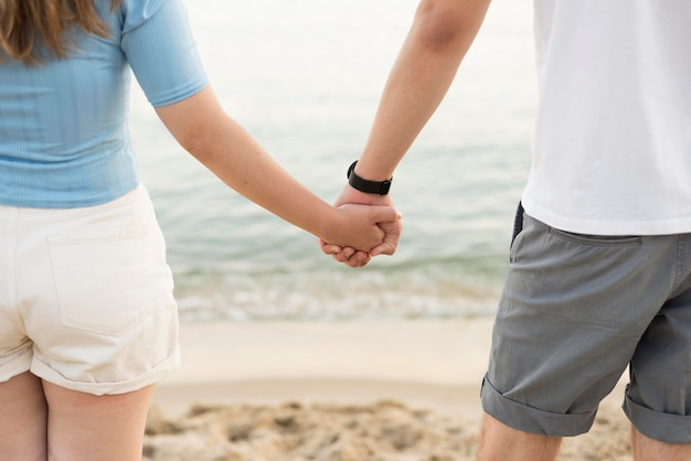 女の子と男の子のビーチのクローズアップに手を繋いで