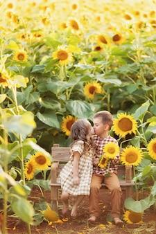 女の子と男の子のベンチにキス、夕暮れに咲くひまわりの中で楽しんで