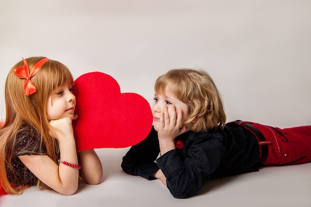 女の子と男の子は彼らの手に心を持つ白い背景の上にあります。