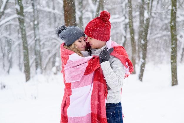 女の子と男の子は冬の森でお互いを温かくします。