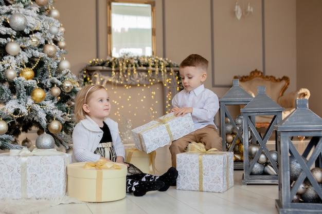 Девочка и мальчик открывают рождественские подарки
