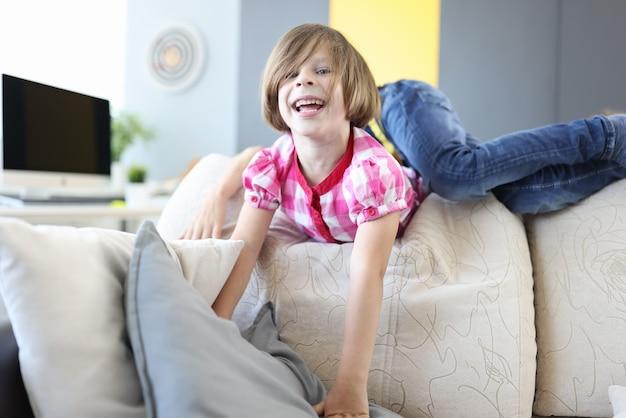 소녀와 소년은 집에서 소파에서 놀고 웃습니다.