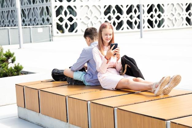 여학생과 남학생들은 콘크리트 벽 사이에 있는 나무 벤치에 학교 배낭을 메고 앉아서 모바일 기기를 사용합니다.