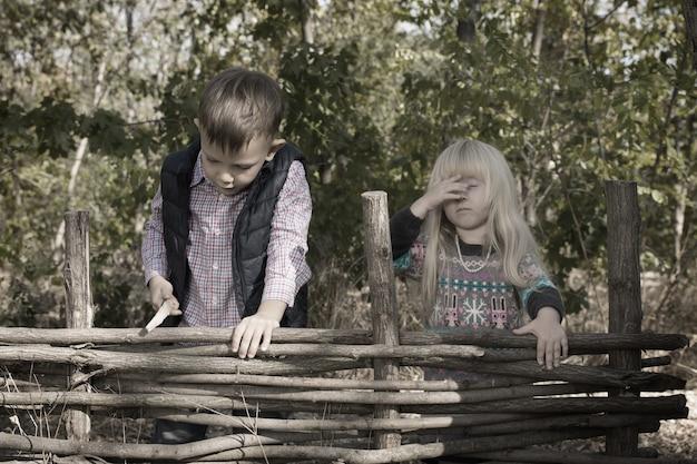 야외에서 소박한 나무 울타리에 서 있는 소녀와 소년