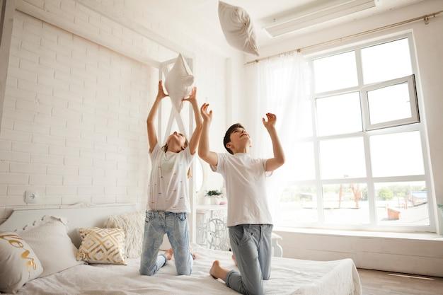 女の子と男の子の自宅のベッドの上に枕を投げる