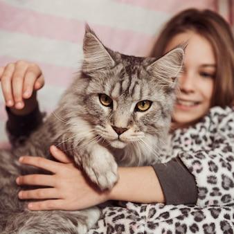 Девушка и кошка сидят в постели