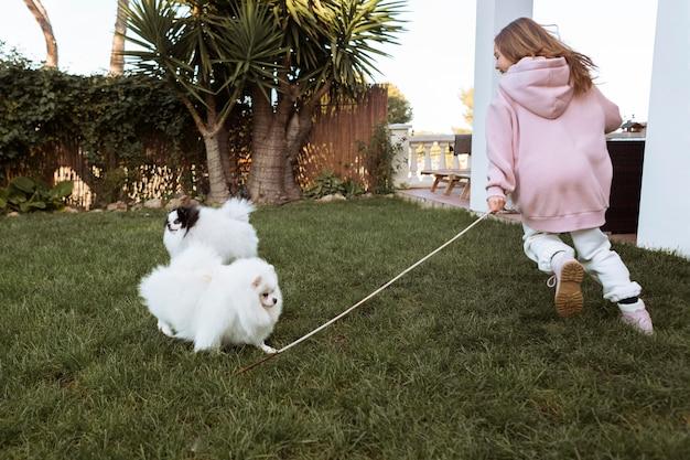 Девочка и милые белые щенки играют в саду