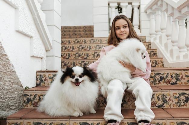Девушка и милые белые щенки сидят на лестнице