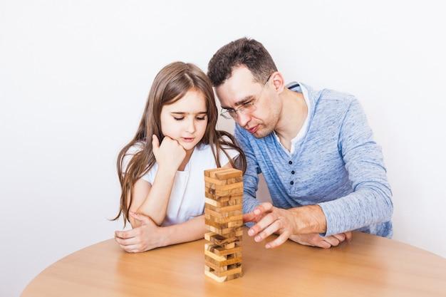 Девочка и папа играют в игру дома, стоят башни из блоков, кубики, дженга, головоломка для развития мозга, умственный интеллект