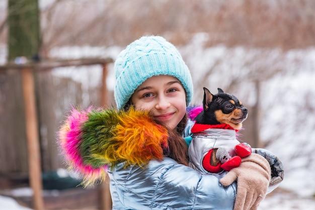 겨울 복장에 소녀와 개. 블루 재킷, 모자와 스카프에 십 대 소녀. 소녀와 치와와