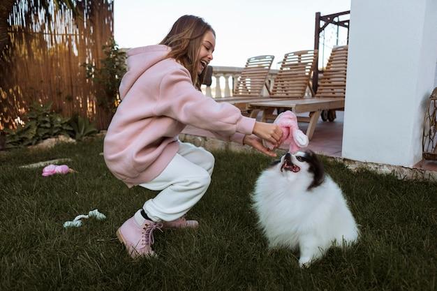 Девушка и собака, играя на открытом воздухе