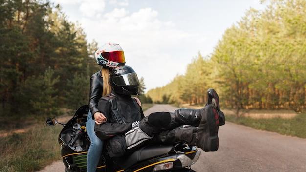 一緒に座って、コピースペースでぼやけた背景に抱き締めるヘルメットのスポーツバイクの女の子と男のモーターサイクリスト