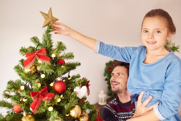 소녀와 크리스마스 트리를 장식하는 그녀의 아빠