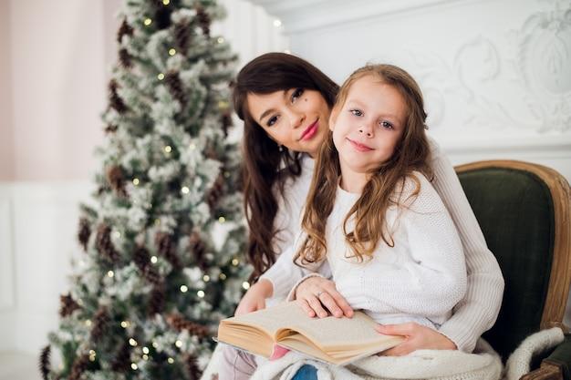 クリスマスに本を読んでいる女の子と彼女のお母さん