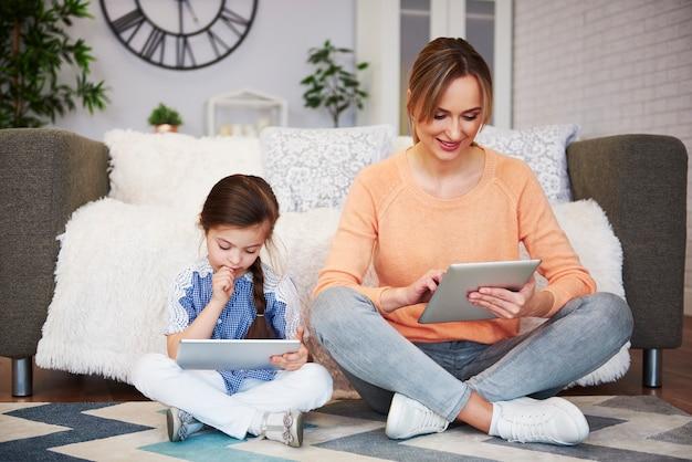 Девушка и ее мама с помощью планшета в гостиной