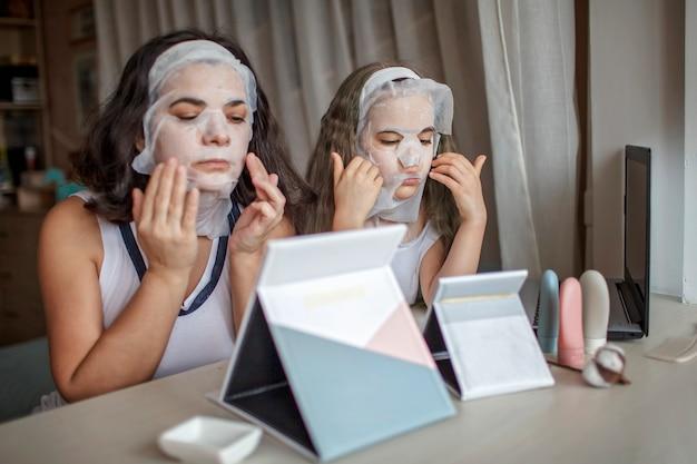 女の子と彼女の母親は、顔の化粧マスクを適用し、鏡の前で楽しんで、自宅の美容院