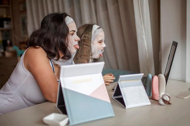 スパの手順中にガジェットを使用している女の子と彼女の母親、インターネットを介してチャットしているママと娘