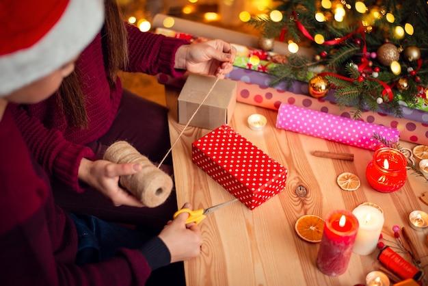 明るい装飾が施されたクリスマスツリーの近くの自宅でクリスマスプレゼントを包む女の子と小さな男の子