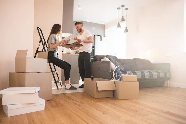 Девушка и мужчина едят пиццу дома. молодые улыбающиеся европейские пары. картонные коробки с вещами. концепция переезда в новую квартиру. идея молодой семьи. интерьер однокомнатной квартиры. солнечный день