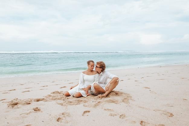 Девушка и мужчина в белой одежде, сидя на белом пляже