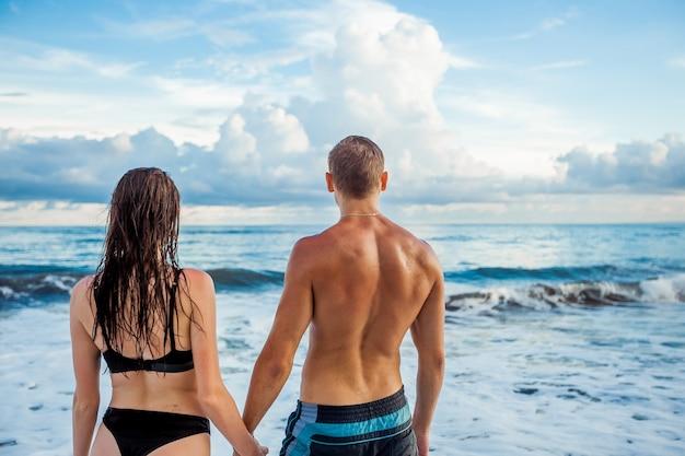 Девушка и мужчина в купальниках находятся на пляже и смотрят на океан, вид сзади, копия пространства