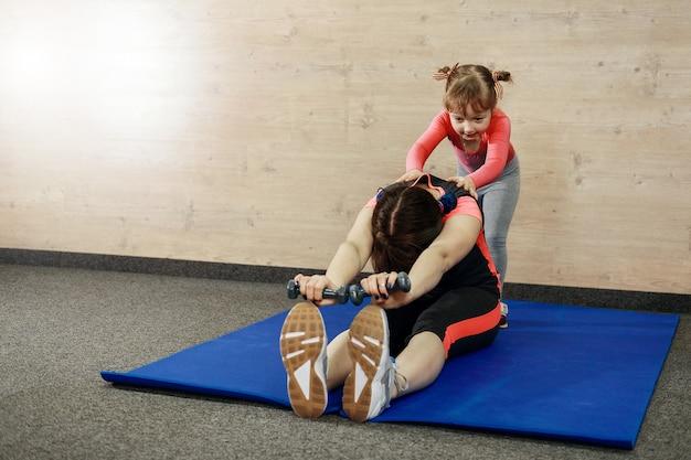 소녀와 엄마는 체육관에서 뻗어있다.