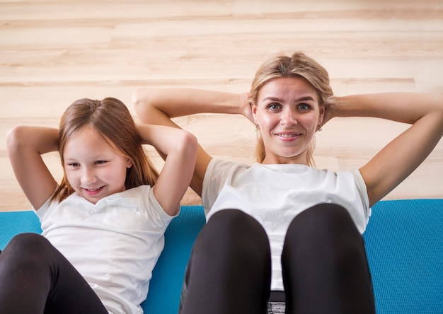 腹部のエクササイズをしている女の子とママ