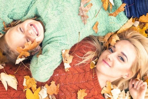 秋の紅葉に横たわる少女とお母さん