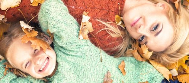 Девушка и мама лежат на осенних листьях