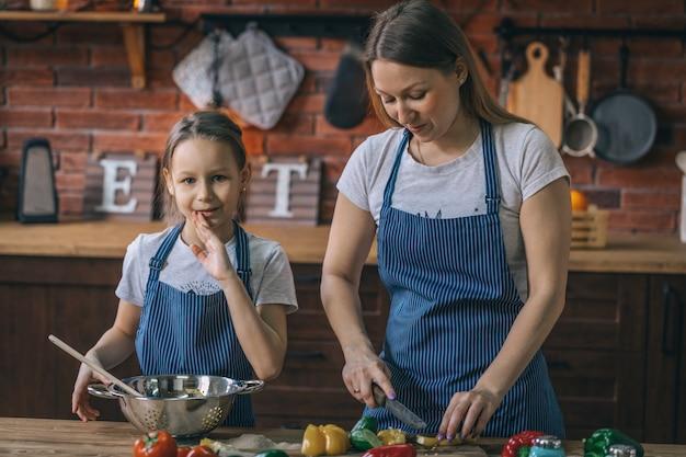 女の子と母親が一緒にサラダを調理