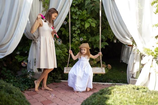Девочка и мать играют на улице в летний день
