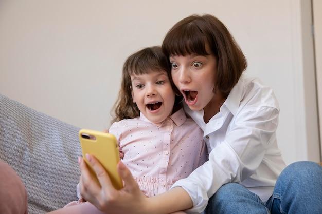 Девушка и мать делают средний снимок селфи Бесплатные Фотографии