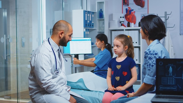 健康診断後にハイファイブをしている少女と小児科医クリニック病院で医療サービスの放射線治療検査を提供する医療の専門医