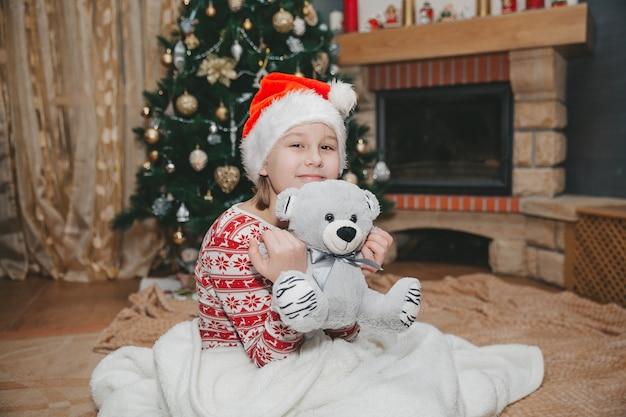 リビングルームのクリスマスツリーで女の子とおもちゃ