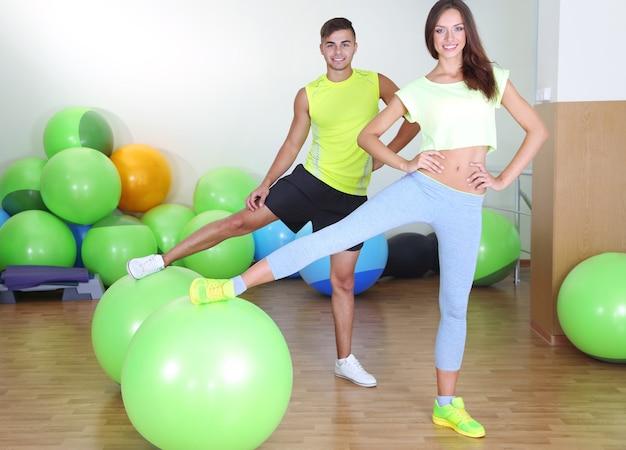Девушка и тренер занимаются в фитнес-зале